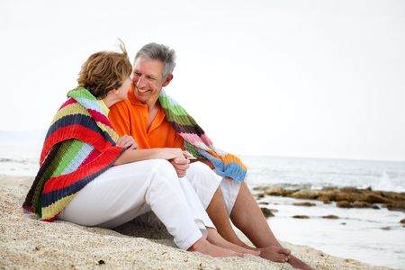mid adults: Happy mature couple sitting on the beach.  Stock Photo