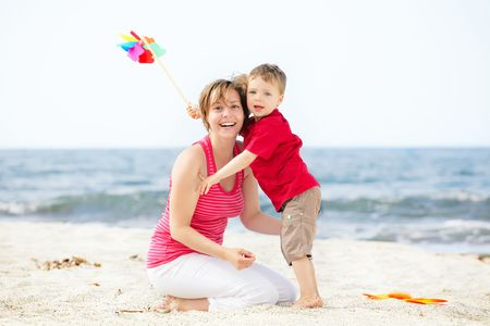 Mother and son having fun on the beach. photo