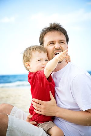 Father and son having fun on the beach. photo