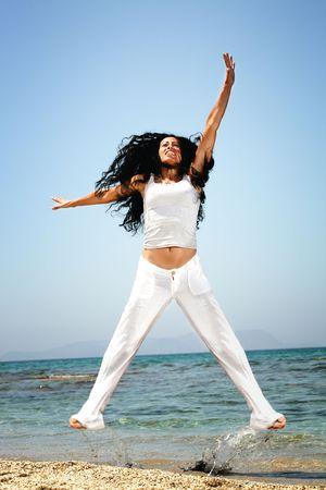 salto largo: Hermosa mujer feliz ejercer en la playa Foto de archivo