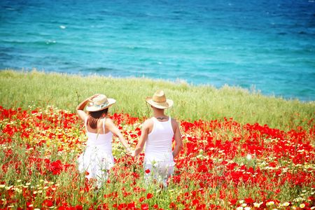 Young happy couple on a meadow full of poppies. photo