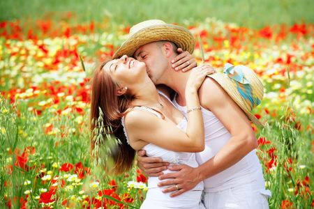 blue romance: Young happy couple on a meadow full of poppies. Stock Photo