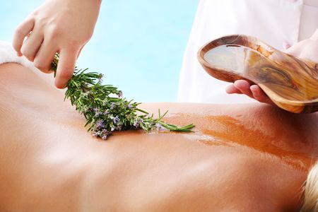 Spa Treatment - woman undergoing  spa treatment with olive oil and herbs. photo