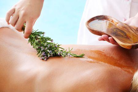 massage oil: Traitement Spa - femme subissant un traitement de spa avec de l'huile d'olive et des herbes.