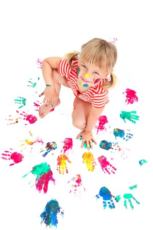 Cute little girl making colorful hand prints. Isolated on white.