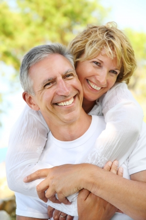 Mature couple smiling and embracing. Focus on the man.