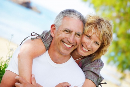 mid adult couples: Close-up portrait of a mature couple smiling and embracing.