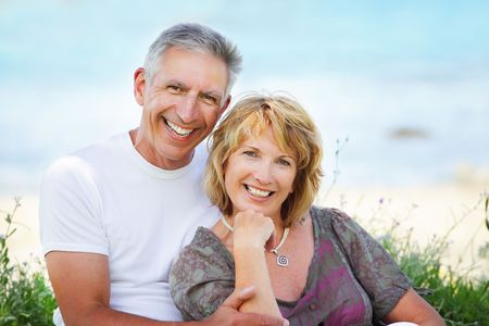 mid adults: Close-up portrait of a mature couple smiling and embracing.