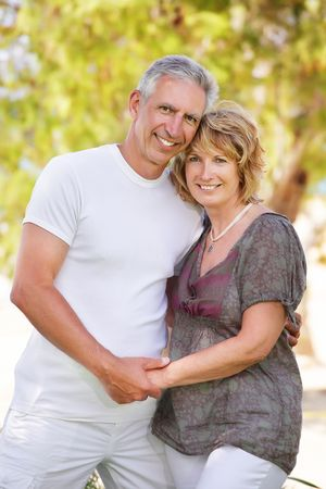 mid adult couples: Mature couple smiling and embracing. Focus on the woman.