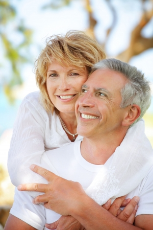 Close-up portrait of a mature couple smiling and embracing.