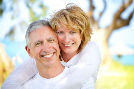 Mature couple smiling and embracing. Focus on the woman. photo