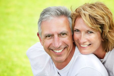 middle adult: Close-up portrait of a mature couple smiling and embracing.