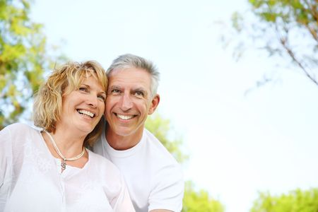 Mature couple smiling and embracing. Focus on the woman.