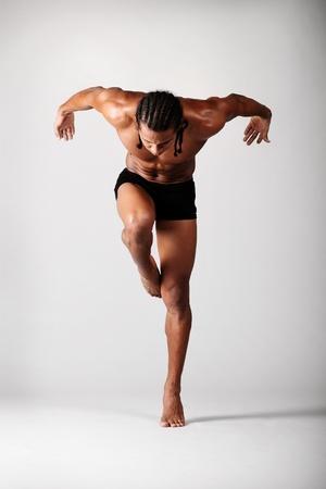 jeune danseur posant sur fond gris
