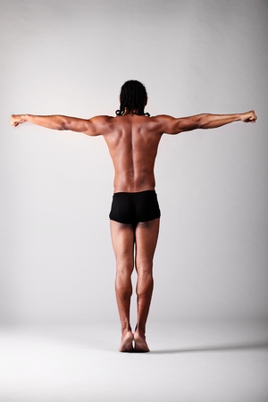 young male dancer posing over grey background