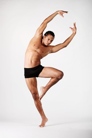 young male dancer posing over grey background photo