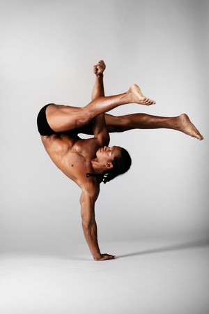 young male dancer posing over grey background Stock Photo - 8974830