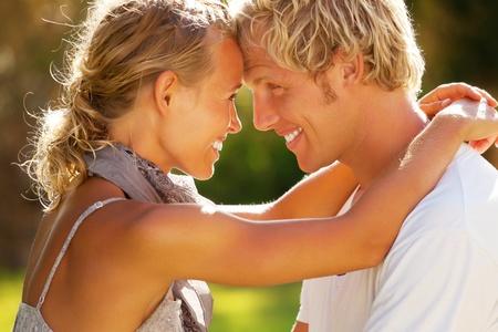 amigos abrazandose: Joven pareja feliz. DOF bajo con el foco en el hombre. Foto de archivo