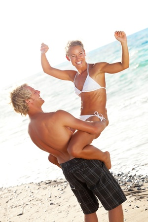 carrying girlfriend: Happy young couple on the beach