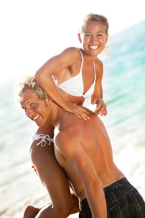 Bonne jeune couple sur la plage de la mise au point sur la fille