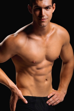 Healthy muscular young man  Isolated on black background   Shallow DoF with focus on chest  photo