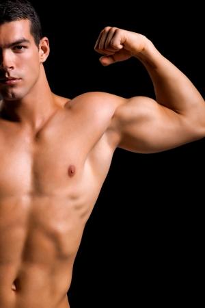 Healthy jeune homme musclé isolé sur fond Shallow DOF noir avec l'accent sur la poitrine et le cou Banque d'images