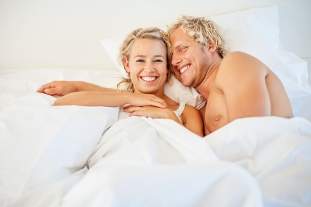 romance bed: Happy young couple in bed Stock Photo