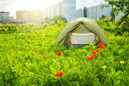 Tent in the city in the background of a multistory building
