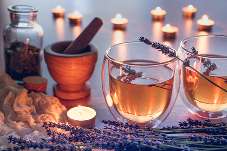 Herbal tea in glass cups with lavender on a wooden kitchen table with lights from candles