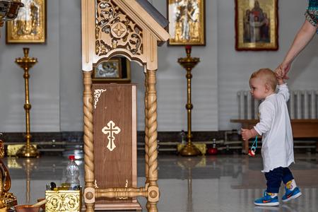 Baby boy with mom in Orthodox Church. Belarus, Starobin, June 23, 2018