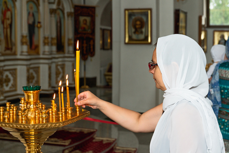 Woman with candle in Orthodox Church. Belarus, Starobin, June 23, 2018 Editorial