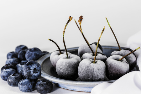 Frozen cherries and blueberries on a kitchen table on white Stockfoto - 122380856