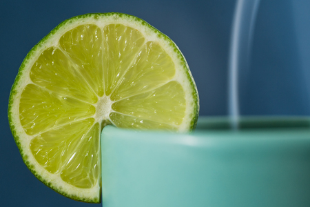 Slice of lime on a tea cup, close up, blue background