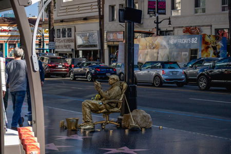 Street artists, driving cars, and tourists walking on Hollywood Boulevard, Los Angeles, October 14, 2016