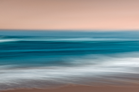 Abstract ocean seascape with blurred panning motion in blue and pink colors
