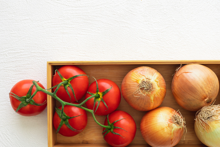 Fresh Red Tomatoes and Onions, Wooden Container, White Background, Close Up, Top View Stockfoto