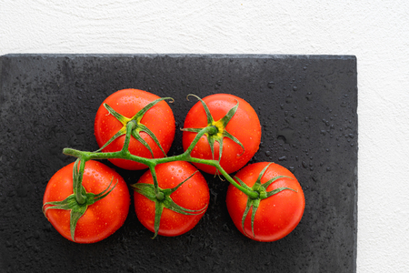 Fresh Red Tomatoes With Drops of Water on a Black Chopping Board in White Background Close Up, Top View