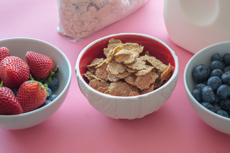 Toasted Oatmeal Flakes with Milk and Fresh Berries, Close up, in Pink Background.  Good Source of Fiber and Vitamins