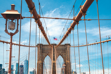 Brooklyn Bridge, American Flag, Cloudy Blue Sky Background. New York City
