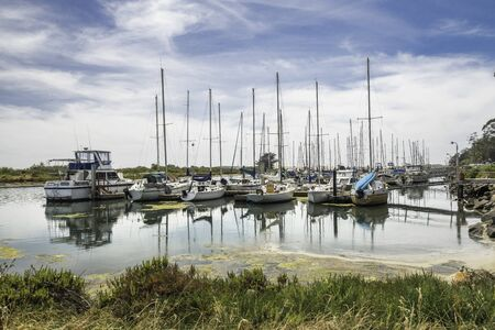 Marina Harbor, Morro Bay, California. Boats, Reflection, Cloudy Blue Sky in Background