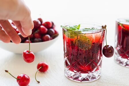 Fresh Cherry Juice in a Glass With Mint Leaves and Ice Close Up on White Background, Woman Hand
