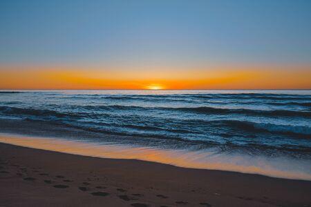 Vista sul mare astratta. Bella spiaggia tropicale al tramonto. Oceano blu, cielo colorato e sole che tramonta all'orizzonte