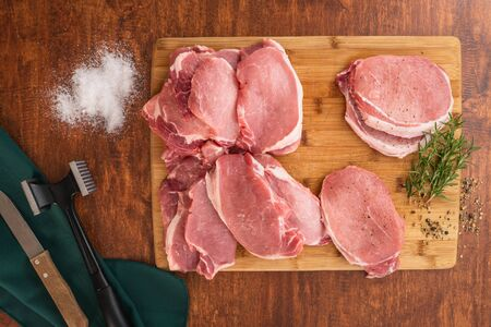 Raw Boneless Pork Loin chops on wooden cutting board with some herbs, salt, and rosemary close up on a wooden rustic background, directly from above