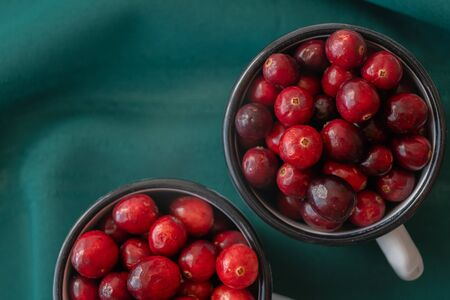 Cranberries. Fresh ripe organic cranberries in a cups directly from above with green background, close up Stock Photo