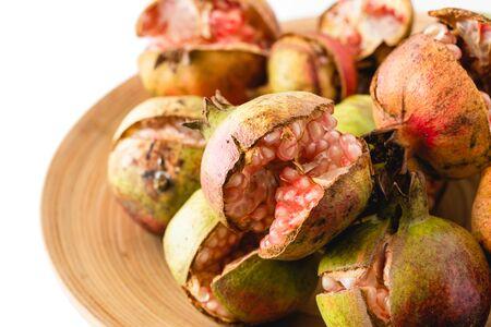 Pomegranates. Cracked fresh ripe organic pomegranates on a wooden plate, close up on white background