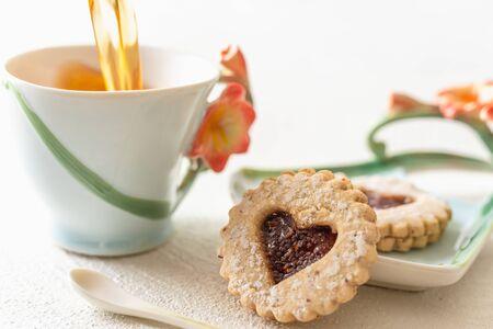Herzförmige Kekse und eine Tasse Tee hautnah auf weißem Hintergrund. Romantisches, glückliches Valentinstag-Konzept Standard-Bild