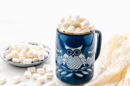 Marshmallow and coffee. Owl-shaped ceramic mug with marshmallows close up on white background, copy space Stock Photo