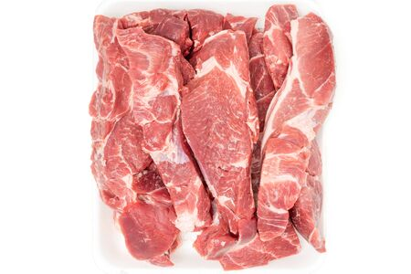 Raw pork meat cuts in white container close up isolated on white background. Fresh slices  without bone, top view.
