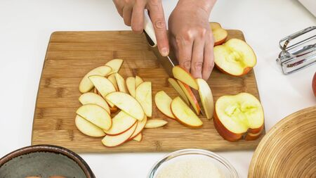 Woman slicing apples. Close up on a wooden cutting board on white background