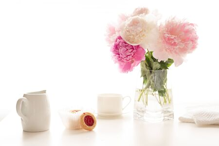 Pink peonies in glass vase, cup of tea, and cookies close up on white kitchen table in morning sunshine. Romantic breakfast, love, wedding, celebration concept
